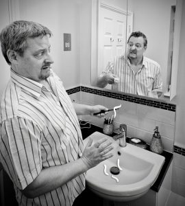 Digital Composite Of Scared Man Looking At His Angry Reflection In Bathroom